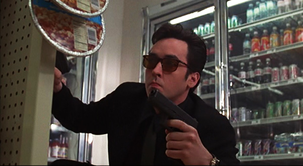 "Professional assassin Martin Blank (John Cusack) takes cover in a convenience store shootout in ""Grosse Pointe Blank,"" a 1997 comedy from Hollywood Pictures."