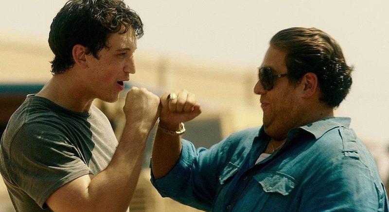 """Gunrunners David Packouz (Miles Teller) and Efraim Diveroli (Jonah Hill) fist-bump after delivering some Berettas to Iraq in """"War Dogs,"""" a 2016 comedy-drama from Warner Brothers."""